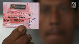 Calon penumpang menunjukan tiket kertas di Stasiun Depok Baru, Jawa Barat, Senin (23/7). Tiket kertas seharga Rp3.000 untuk semua stasiun tersebut diberlakukan selama masa pembaharuan dan pemeliharaan sistem e-Ticketing. (Liputan6.com/Immanuel Antonius)