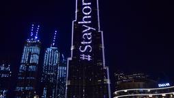 """Pencakar langit Burj Khalifa menyala dengan pesan """"Stay Home"""" di Dubai pada Selasa (24/3/2020). Gedung pencakar langit tertinggi di dunia itu menyala dengan slogan kampanye #STAYHOME yang mendesak warga untuk mematuhi langkah-langkah pencegahan di tengah pandemi COVID-19. (Giuseppe CACACE/AFP)"""
