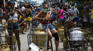 Warga memakai masker saat antre membeli gas murah dari Petrobrás Oil Tankers Union di favela Vila Vintem, Rio de Janeiro, Brasil, Jumat (12/3/2021). Kegiatan ini sebagai kampanye solidaritas untuk memperingati Hari Perjuangan Nasional Pertahanan Perusahaan Milik Negara. (AP Photo/Bruna Prado)
