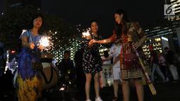 Warga menyalakan kembang api saat car free night pada malam pergantian tahun di Jalan MH Thamrin, Jakarta, Senin (31/12). Hujan yang mengguyur Jakarta sejak siang tidak menyurutkan antusias warga menikmaticar free night. (Liputan6.com/Angga Yuniar)