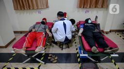 """Petugas PMI mengambil darah pendonor sukarela di Jalan Kramat Raya, Jakarta, Kamis (30/4/2020). PMI menyatakan selama penerpan """"physical distance"""" untuk menekan penyebaran COVID-19, jumlah pendonor sukarela berkisar 100 sampai 200 orang per hari atau turun 90 persen. (Liputan6.com/Faizal Fanani)"""