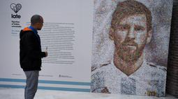 Pengunjung mengamati mural Lionel Messi di Casa Rosada Museum, Buenos Aires, Argentina, Rabu (20/6). Mural terbuat dari dua ribu stiker figur pemain Argentina dalam Piala Dunia sepanjang masa. (Eitan ABRAMOVICH/AFP)