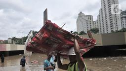 Petugas Pusat Pengelolaan Kompleks (PPK) Kemayoran membersihkan sampah yang muncul akibat banjir di Underpass Kemayoran, Jakarta, Minggu (2/2/2020). Selain melumpuhkan akses, banjir setinggi hingga 5 meter tersebut menyebabkan sampah memenuhi Underpass Kemayoran. (merdeka.com/Iqbal S. Nugroho)