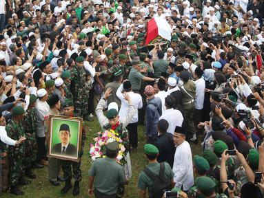 Pelayat mengangkat keranda jenazah tokoh PBNU KH Hasyim Muzadi jelang pemakaman di Ponpes Al-Hikam, Kukusan, Beji, Depok, Kamis (16/3). Jenazah KH Hasyim Muzadi dimakamkan secara militer dengan iringan lantunan tahlil. (Liputan6.com/Immanuel Antonius)