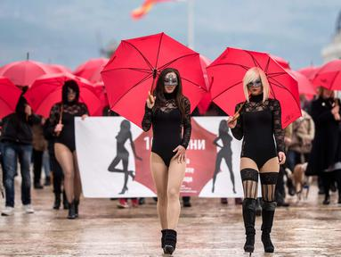 Sejumlah wanita pekerja seks menggenakan busana hitam dan topeng serta membawa payung merah berunjuk rasa di Skopje (17/12). Para pekerja seks ini memprotes kekerasan yang mereka alami, dan hukuman untuk klien prostitusi. (AFP Photo/Robert Atanasovski)