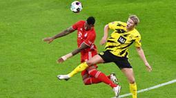 Bek Bayern Munchen, Jerome Boateng, duel udara dengan striker Borussia Dortmund, Erling Haland, pada laga Bundesliga di Stadion Signal Iduna Park, Sabtu (7/11/2020). Bayern menang dengan skor 3-2. (Bernd Thissen/Pool via AP)