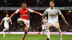 Penyerang Arsenal, Alexis Sanchez (kiri) mengontrol bola dari kejaran Bek Swansea City Federico Fernandez saat Laga Liga Premier Inggris di Emirates Stadium, Selasa (12/5/2015). Swansea City menang 1-0 atas Arsenal. (Reuters/ADylan Martinez)