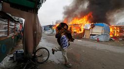 """Seorang imigran berjalan melewati kobaran api di pengungsian imigran """"Jungle"""", di kota pelabuhan Calais, Prancis (26/10). Pengosongan kamp ini sempat mendapat penolakan dari beberapa imigran. (REUTERS/Philippe Wojazer)"""