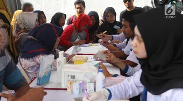 Warga mendapatkan pengobatan gratis pada kegiatan bakti sosial di Lapangan Merdeka, Balikpapan, Kalimantan Timur, Selasa (23/7/2019). Pertamina bekerja sama dengan Bhayangkari mengadakan bakti sosial di wilayah Balikpapan dalam rangka Hari Kesatuan Gerak Bayangkari ke-67. (Liputan6 com/Angga Yuniar)