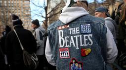 Seorang penggemar mengenakan jaket The Beatles saat menghadiri peringatan 36 tahun kematian John Lennon di New York, AS (8/12). Strawberry Fields adalah sebuah tempat yang didedikasikan untuk mengenang mendiang John Lennon. (Reuters/Mark Kauzlarich)