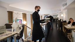 Pelayan berjalan melewati sebuah maneken yang mengenakan busana kreasi desainer lokal di sebuah restoran di Kota Tua Vilnius, Lithuania, Kamis (21/5/2020). Sejumlah restoran dan kafe di Lithuania memamerkan koleksi busana karya desainer lokal yang terdampak COVID-19. (Xinhua/Alfredas Pliadis)
