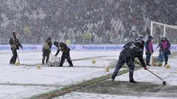 Pekerja membersihkan salju di Allianz Stadium di Turin, Italia, (25/2). Juventus kini berada di posisi kedua dengan 65 poin, selisih satu poin dengan Napoli di puncak klasemen. (Alessandro Di Marco / ANSA via AP)