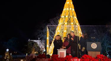 Presiden AS Barack Obama (kedua kanan) didampingi Michele Obama, dan dua putrinya menyalakan Pohon Natal Nasional di Taman Ellipse, dekat Gedung Putih, Washington, Kamis (3/12). Acara tersebut menandai dimulainya musim Natal. (AFP PHOTO/JIM WATSON)