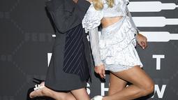 Paris Hilton bersama adiknya Nicky Hilton Rothschild berpose menghadiri Savage x Fenty selama New York Fashion Week di Barclays Center di New York City (10/9/2019). Nicky tampil cantik mengenakan gaun navy terstruktur dengan kain bergaris dengan sepasang stiletto hitam klasik. (AP Photo/Evan Agostin