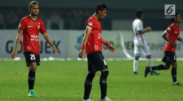 Pemain Persija, Maman Abdurrahman dan M Rezaldi Hehanusa meninggalkan lapangan usai melawan Bali United pada lanjutan Liga 1 Indonesia di Stadion Patriot Candrabhaga, Minggu (21/5). Laga kedua tim berakhir imbang 0-0. (Liputan6.com/Helmi Fithriansyah)