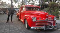Suami Soimah bercerita tentang koleksi Ford 1946 yang dipajang saat Hotrod Weekend Party di halaman parkir Hotel Melia Purosani Yogyakarta. (Liputan6.com/ Switzy Sabandar)
