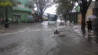 Jalan raya yang tergenang banjir menjadi area berenang dan area bermain anak-anak di Garut, Jawa Barat (Liputan6.com/Jayadi Supriadin)