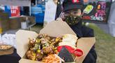 Penjual yang mengenakan masker memperlihatkan hidangan ayam goreng saat Festival Ayam Goreng di Toronto, Kanada, 20 September 2020. Festival yang digelar di tengah pandemi COVID-19 tersebut berlangsung pada 19-20 September 2020 dengan menghadirkan sekitar 30 jenis ayam goreng. (Xinhua/Zou Zheng)