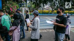 Warga antre untuk mengambil Bantuan Sosial Tunai (BST) di SMAN 111, Jakarta, Selasa (19/1/2021). Pemprov DKI Jakarta menyalurkan BST sebesar Rp 300 ribu kepada 1.055.216 KK mulai Januari hingga April 2021. (Liputan6.com/Faizal Fanani)