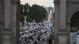 """Para peserta dalam balutan serba putih  berkumpul untuk Dinner en Blanc atau """"makan malam putih"""" di Tuileries Gardens, Paris, Kamis (6/6/2019). Mereka berkumpul untuk menggelar makan malam terbuka, yang berlangsung di tempat berbeda di Paris setiap tahun. (Lucas BARIOULET/AFP)"""