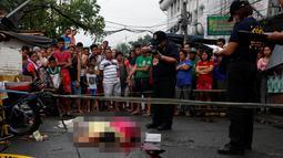 Aparat polisi Manila mengambil gambar jenazah Nora Acielo yang tewas ditembak orang tak dikenal di Manila, Filipina, Kamis (8/12). Acielo ditembak saat sedang mengantarkan kedua anaknya berangkat sekolah. (REUTERS/Erik De Castro)