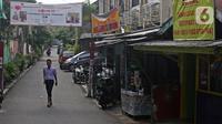 Warga melintasi spanduk zona merah kawasan RW 04 Kelurahan kalibata, Jakarta, Selasa (9/2/2021). Pemerintah mulai menerapkan PPKM skala mikro mulai 9-22 Februari 2021 untuk provinsi yakni DKI Jakarta, Jawa Barat, Banten, Jawa Tengah, Yogyakarta, Jawa Timur, dan Bali. (Liputan6.com/Herman Zakharia)