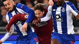 Gelandang AS Roma Nicolo Zaniolo (tengah) terjepit saat berusaha melewati pemain FC Porto Alex Telles dan Danilo Pereira dalam babak 16 besar Liga Champions di Stadion Olimpico, Roma, Italia, Selasa (12/2). AS Roma menang 2-1. (Alberto PIZZOLI/AFP)