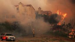 Petugas pemadam kebakaran berjuang memadamkan kobaran api di Pacific Coast Highway, Malibu, California, AS, Jumat (9/11). Api Woolsey menjalar ke jalan raya dan menuju kota pesisir, termasuk kawasan wisata Malibu dan Calabasas. (AP Photo/Reed Saxon)