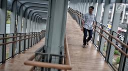 Pejalan kaki melintas di jembatan penyeberangan orang (JPO) Bundaran Senayan, Jakarta, Senin (21/1). JPO Bundaran Senayan mengedepankan konsep minimalis modern. (Liputan6.com/Faizal Fanani)