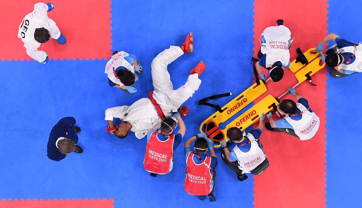 Atlet Jerman Jonathan Horne mendapat perawatan dari petugas medis setelah cedera saat melawan Gogita Arkania dari Georgia dalam pertandingan karate pada Olimpiade Tokyo 2020 di Nippon Budokan, Tokyo, Sabtu (7/8/2021). (Foto: AFP/Alexander Nemenov)