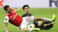 Gelandang Arsenal, Dani Ceballos, dijatuhkan gelandang Eintracht Frankfurt, Daichi Kamada, pada laga Europa League di Frankfurt, Kamis (19/9). Frankfurt kalah 0-3 dari Arsenal. (AFP/Daniel Roland)
