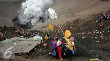 Warga berebut uang dan hasil bumi yang dilemparkan dari bibir kawah Gunung Bromo, Probolinggo, Kamis (21/7). Warga Tengger melakukan ritual lempar hasil bumi sebagai wujud syukur pada Sang Hyang Widi. (Liputan6.com/Helmi Fithriansyah)