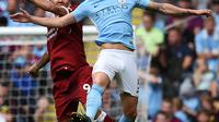 Pemain Manchester City John Stones berebuta boal diudara dengan Roberto Firmino saat pertandingan Manchester City menjamu Liverpool di Stadion Etihad, Manchester (9/9). (AFP Photo/Oli Scarff)