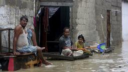 Warga duduk di luar rumah mereka di jalan banjir setelah hujan deras, di Karachi, Pakistan, Selasa (30/7/2019). Hujan deras yang melanda kota Karachi, pelabuhan selatan Pakistan, memicu banjir dan menewaskan enam orang. Pihak berwenang menutup sekolah. (AP/Photo/Fareed Khan)