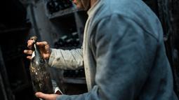 """Seorang pria memegang botol anggur """"Vin Jaune"""" tahun 1774 di Arbois, Perancis timur (22/5). Tiga botol anggur produksi tahun 1774 akan dijual pada 26 Mei 2018, selama lelang. (AFP Photo/Sebastian Bozon)"""