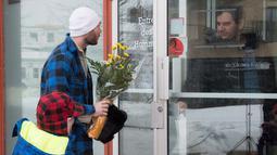Seorang pria bersama anaknya membawa bunga untuk diberikan kepada jemaah di Masjid Quebec, Kanada, (2/2). Akibatnya penembakan enam orang tewas dan 12 orang lain menderita luka ringan. (Jacques Boissinot/The Canadian Press via AP)