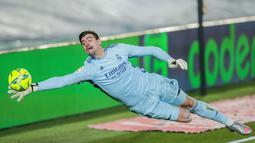 Kiper Real Madrid, Thibaut Courtois, menghalau bola yang mengarah ke gawangnya saat melawan Athletic Bilbao pada laga Liga Spanyol di Stadion Alfredo Di Stefano, Rabu (16/12/2020). Real Madrid menang dengan skor 3-1. (AP/Bernat Armangue)