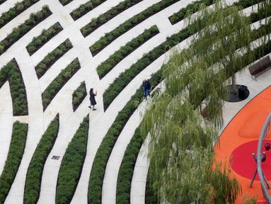 Pengunjung menyusuri jalan saat pembukaan 'Perpustakaan Pohon' di Milan, Italia, Sabtu (27/10). Perpustakaan ini memiliki luas hampir 10 hektare. (AP Photo/Luca Bruno)