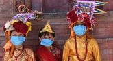 Anak-anak Nepal mengenakan masker dan kostum sapi tradisional saat berpartisipasi dalam prosesi 'Gai Jatra', atau festival sapi, di Kathmandu, Selasa (4/8/2020). Festival ini untuk meminta keselamatan dan kedamaian bagi orang yang mereka cintai yang telah meninggal. (PRAKASH MATHEMA/AFP)