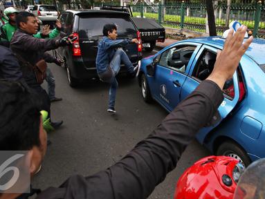 Pengendara ojek online merusak dan melakukan sweeping di kawasan Senayan, Jakarta, Selasa (22/3). Pascabentrok ojek online melakukan sweeping dan perusakan terhadap taksi serta bajaj yang melintas di kawasan tersebut. (Liputan6.com/Immanuel Antonius)