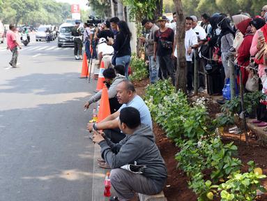 Sejumlah warga berdiri di sisi jalan TMP Kalibata untuk melihat prosesi pemakaman Presiden RI ke-3 BJ Habibie, Jakarta, Kamis (12/9/2019). BJ Habibie meninggal dunia setelah menjalani perawatan di RSPAD dan akan dimakamkan di Taman Makam Pahlawan Kalibata. (Liputan6.com/Helmi Fithriansyah)
