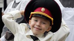 Seorang taruna muda tersenyum ketika menghadiri upacara pada hari pertama sekolah di salah satu sekolah Kadet terbaik, lyceum, di Kiev, Senin (3/9). Ukraina menandai Hari Pengetahuan, sebagai dimulainya tahun ajaran baru. (AP Photo/Efrem Lukatsky)