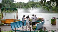 Wisatawan berfoto saat mengunjungi Senayan Park, Jakarta, Rabu (9/12/2020). Libur Nasional Pilkada Serentak 2020 dimanfaatkan sebagian warga Jakarta dan sekitarnya untuk mengunjungi tempat rekreasi bersama keluarga. (Liputan6.com/Faizal Fanani)