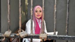 Artis Eddies Adelia sempat menyapa wartawan dari balik sel saat tengah menunggu persidangan dimulai, Jakarta, Rabu (12/11/2014). (Liputan6.com/Panji Diksana)