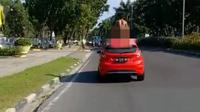 Pria telanjang diduga orang gila naik ke atas mobil yang dikendarai dokter di Jalan Jenderal Sudirman, Pekanbaru. (Liputan6.com/M Syukur)