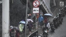 Pekerja dan pengendara berteduh saat hujan deras mengguyur kawasan Gatot Soebroto, Jakarta, Senin (11/2). Badan Meteorologi, Klimatologi, dan Geofisika (BMKG) memprediksi puncak musim hujan terjadi hingga Februari 2019. (Merdeka.com/Iqbal Nugroho)