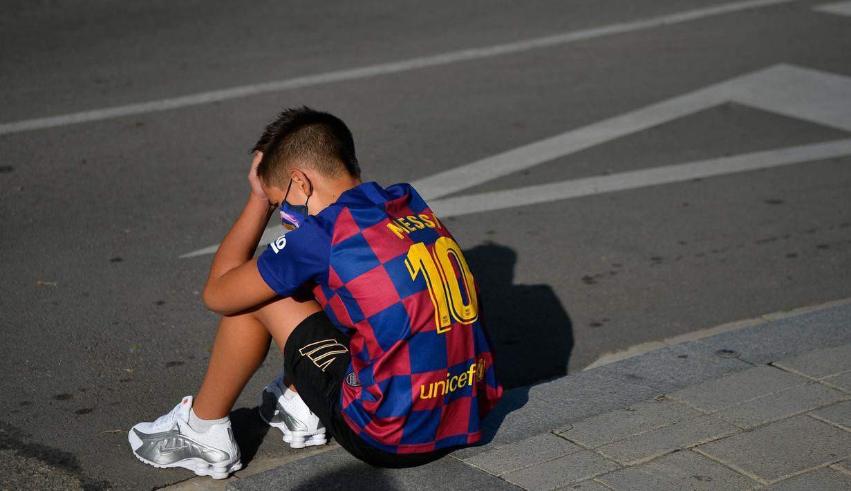 Seorang bocah tertunduk lesu saat menunggu Lionel Messi di lokasi latihan Barcelona, Senin (31/8/2020). Messi secara mengejutkan tidak datang untuk mengikuti tes swab Covid-19 yang dijadwalkan Barcelona. (AFP/Pau Barrena)