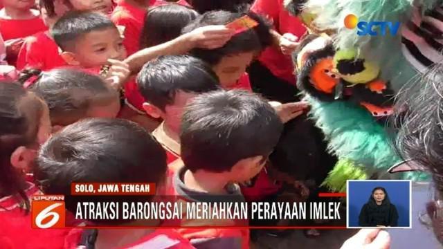 Atraksi barongsai di Solo, Jawa Tengah, pukau ratusan siswa SD yang tengah menyaksikan. Para siswa tersebut pun antusias berebut memasukkan angpau ke dalam mulut barongsai.