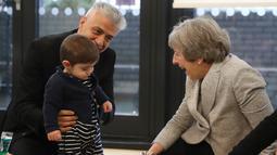 Perdana Menteri Inggris Theresa May tertawa saat bermain dengan bayi di pusat kesehatan di London, Inggris, Kamis (22/11). Sebelum menjabat sebagai PM Inggris, Theresa aktif menjadi menteri sejak tahun 2004. (Andrew Matthews/Pool via AP)