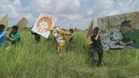 Komunitas Tiger Heart sedang mengangkat mural yang dituangkan dalam media tripleks. (Liputan6.com/ Gresi Plasmanto)